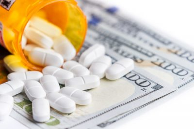 close up of a prescription bottle of opioids with white tables falling out on top of a group of hundred dollar bills