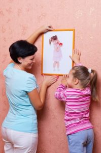 mom and daurgter hanging picture of daughter on wall in house